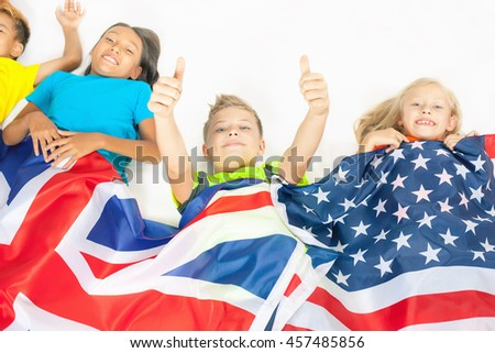 Funny kids holding flag of Great Britain and american national flag. Group of school children. Multiethnic students. Back to school. Friends. Fans. White background - stock photo