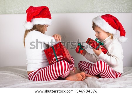 funny kids in their pajamas and Christmas caps on the bed, Christmas and New Year concept, with gifts