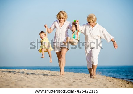 funny kids walking with her mother and grandmother on the beach in summer - stock photo