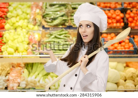 Funny Lady Chef with Big Spoon Presenting Fresh Vegetables - Young female cook in a grocery store presenting healthy menu options   - stock photo