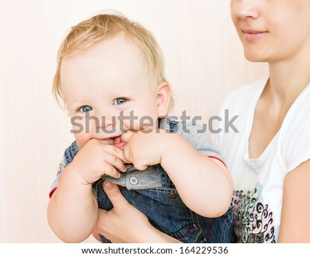 Funny laughing baby boy at his mother hands - stock photo