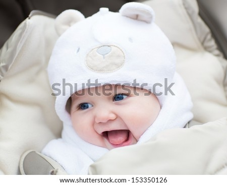 Funny laughing baby in a teddy bear hat sitting in a stroller on c old winter day - stock photo