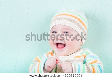 Funny laughing girl in a knitted sweater and hat on a green blanket - stock photo