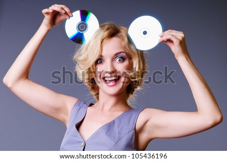 funny laughing young woman with two CDs in her hands. portrait on gray background