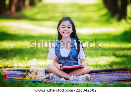 Funny little Asian girl learning with tablet pc in the park - stock photo