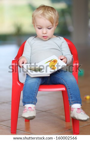 Funny little baby girl sitting indoors on a small red plastic chair reading children book about animals - stock photo