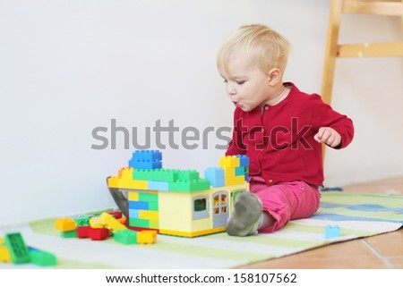 Funny little baby girl sitting on a carpet indoors playing with colorful building bricks