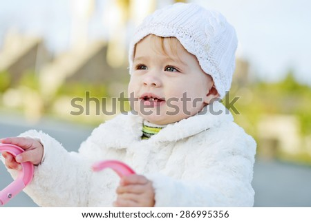 funny little baby girl with stroller outdoors - stock photo