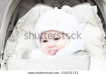 Funny little baby in a teddy bear hat showing its tong sitting in a stroller on a cold winter day - stock photo