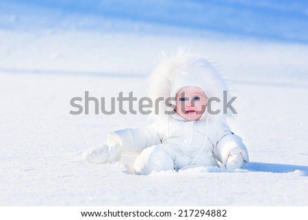 Funny little baby playing in snow on a sunny winter day - stock photo