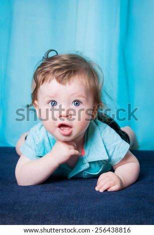 Funny little baby smiling. Beautiful kid lies on a mattress in a turquoise shirt and looking with great interest in the frame