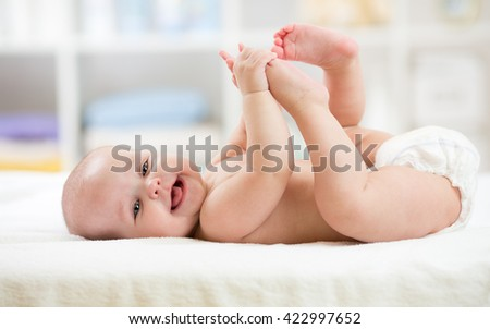 Funny little baby wearing a diaper playing on bed in nursery room. Happy child after bath or shower. Infant kid diaper change and skin care. Smiling kid playing with his feet. - stock photo