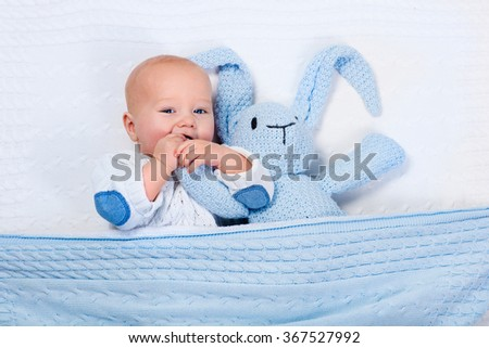 Funny little baby wearing a warm knitted jacket playing with toy bunny relaxing on white cable knit blanket in sunny nursery. Kids winter clothing and bedding. Hand made toys and textile for children. - stock photo
