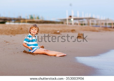 Funny little blond kid boy having fun with building sand castle on the beach of ocean or sea by sunset. Happy child spending active vacations. - stock photo