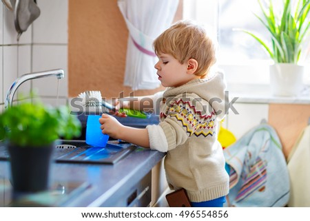 Funny Little Blond Kid Boy Washing Dishes In Domestic Kitchen Happy Child Having Fun With