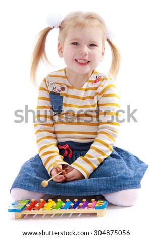 Funny little blonde girl with pigtails on her head sitting on the floor in kindergarten and plays the xylophone. She knocks the hammer on the keys-Isolated on white background - stock photo