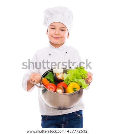 funny little boy-cook in uniform holding bowl with vegetables in hands isollated on white background