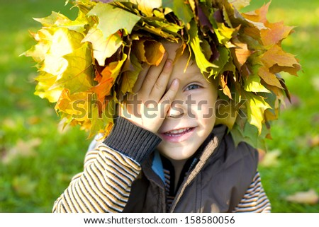 Funny little boy covered his eyes with his hand - stock photo