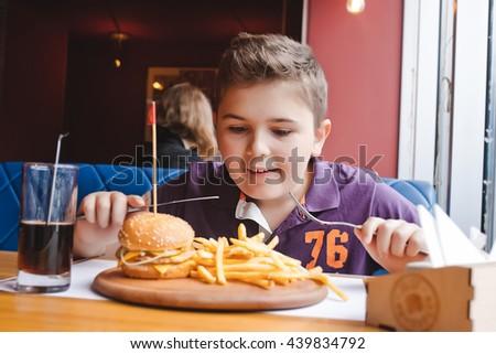funny little boy eating a hamburger at a cafe, food concept