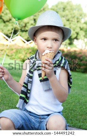 Funny little boy eating ice-cream outdoors in summer park - stock photo
