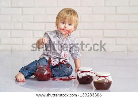 Funny little boy got messy eating strawberry jam from glass jars