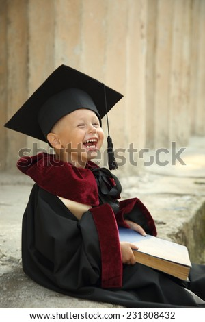 funny little boy graduate of the University - stock photo