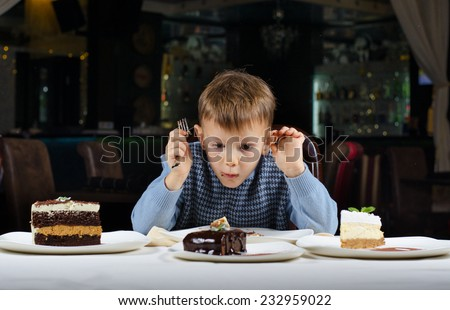 Funny little boy mesmerised by an assortment of cakes displayed on the dining table in front of him as he tries to make a choice where to begin eating - stock photo