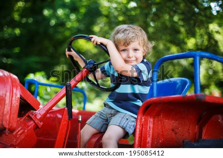 Funny little boy of three years playing on tractor in summer, outdoors - stock photo