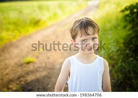 funny little boy on a country road with an innocent expression on his face - stock photo