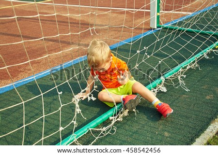 funny little boy on playground. playing child on sports ground