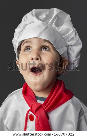 Funny, little boy preparing healthy food on kitchen over grey background, cook hat