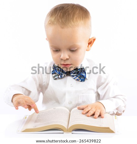 funny little boy sitting at the table and a book review. portrait on white background.
