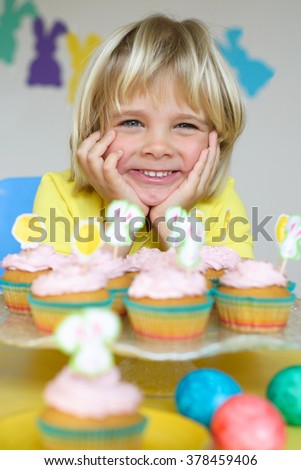 Funny little boy with cupcakes in Easter scene