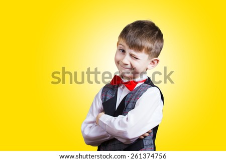 Funny little boy with one eye closed isolated over yellow background. - stock photo