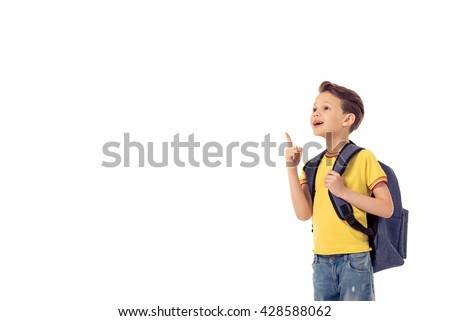 Funny little boy with school backpack is smiling, looking and pointing upward, isolated on a white background - stock photo
