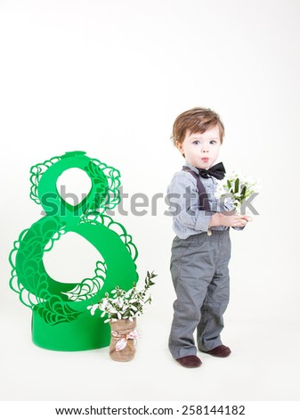 Funny little boy with snowdrops in hand stands and smiles - stock photo