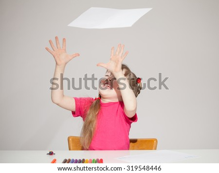 Funny little catching a sheet of paper, grey background - stock photo