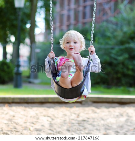 Funny little child, adorable preschooler girl in pretty dress having fun on a swing in the park on summer day - stock photo