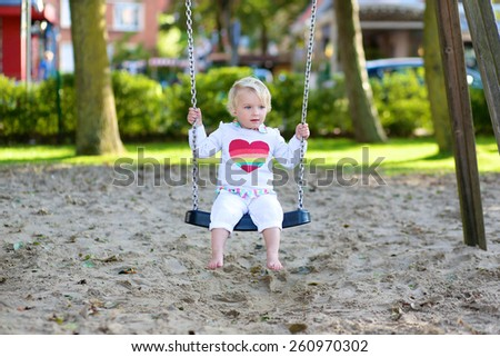 Funny little child, adorable preschooler girl in pretty dress having fun playing on a swing in the park on summer day