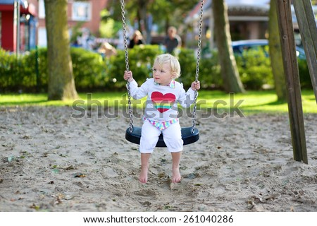 Funny little child, adorable preschooler girl in pretty dress having fun playing on a swing in the park on summer sunny day
