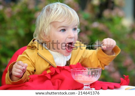Funny little child, adorable toddler girl, eating delicious ice cream sitting comfortable in cozy outdoors cafe wrapped in warm red plaid on sunny autumn day - stock photo