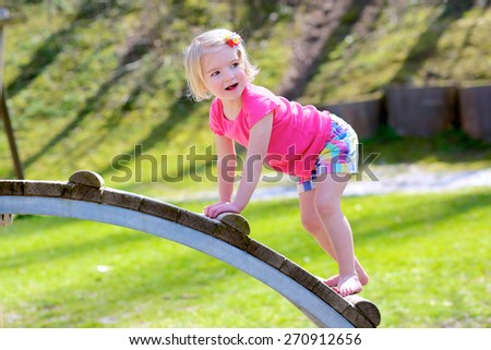 Funny little child, blond sportive toddler girl in casual outfit, having fun climbing on playground in the park on a sunny spring or summer day - stock photo