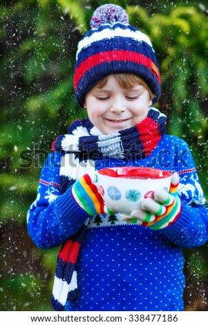 Funny little child holding big cup with snowflakes and hot cocoa and chocolate drink and marshmallows. Kid boy in winter sweater, cap, scarf and colorful gloves. On cold winter day during snowfall. - stock photo
