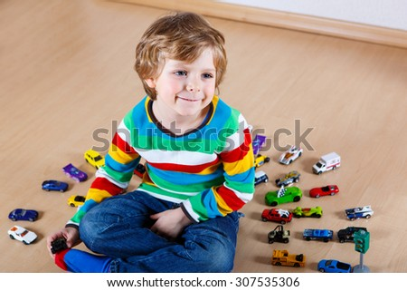 Funny little child playing with lots of toy cars indoor, at home or at nursery. Kid boy wearing colorful shirt and having fun. People, Lifestyle, Family concept. - stock photo