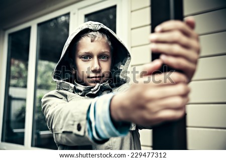 Funny little child with jacket playing near a house looking into camera  - stock photo