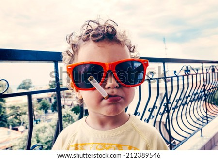 Funny little child with sunglasses and cigarette.Selective focus on the child - stock photo