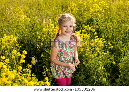 Funny little girl among yellow wildflowers in the summer