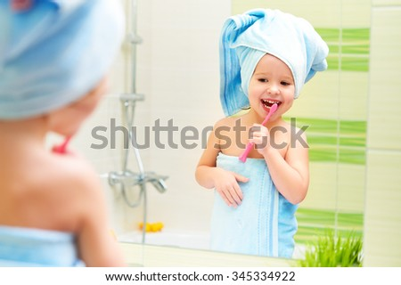 funny little girl cleans teeth with a toothbrush in the bathroom - stock photo