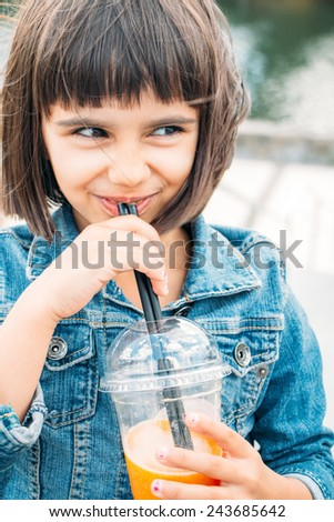Funny little girl drinking a fruit smoothie in the street