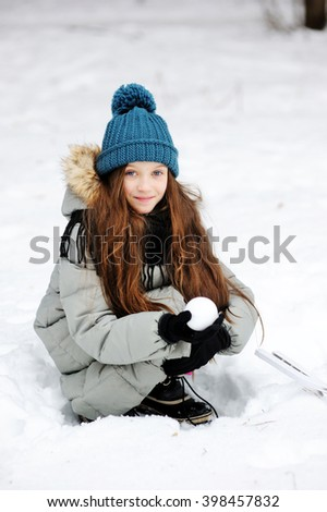 Funny little girl having fun in beautiful winter park with snowballs - stock photo